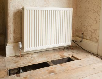 New radiator fitted in old house showing pipework and floorboards